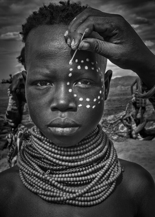 Kunstfotografi Painting the face of a karo tribe girl (Omo Valley-Ethiopia)