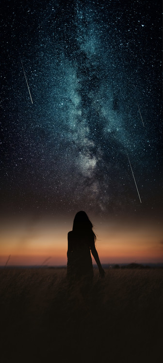 Exklusiva konstfoton Dramatic and fantasy scene with young woman looking universe with falling stars.