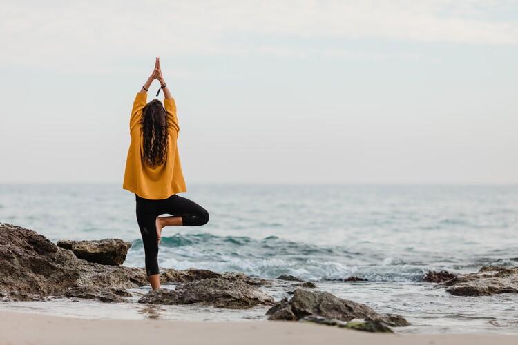 practicing yoga at beach Fotobehang