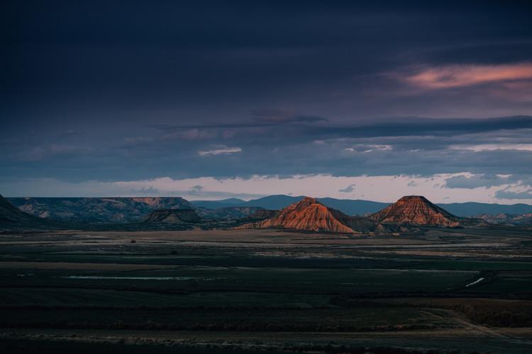 Fotografia d'arte Two desert elevations with a susnet clouds