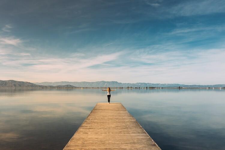 Ekskluzivna fotografska umetnost Woman doing yoga in the harbor
