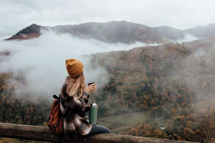 Ekskluzivna fotografska umetnost Woman having breakfast in the mountains in autumn