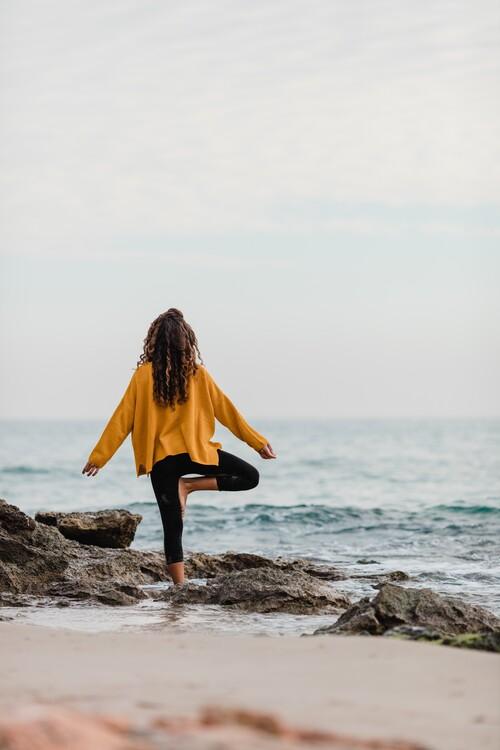 Fototapeta practicing yoga at beach
