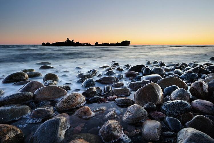 Glasbilder Stones on the Shore